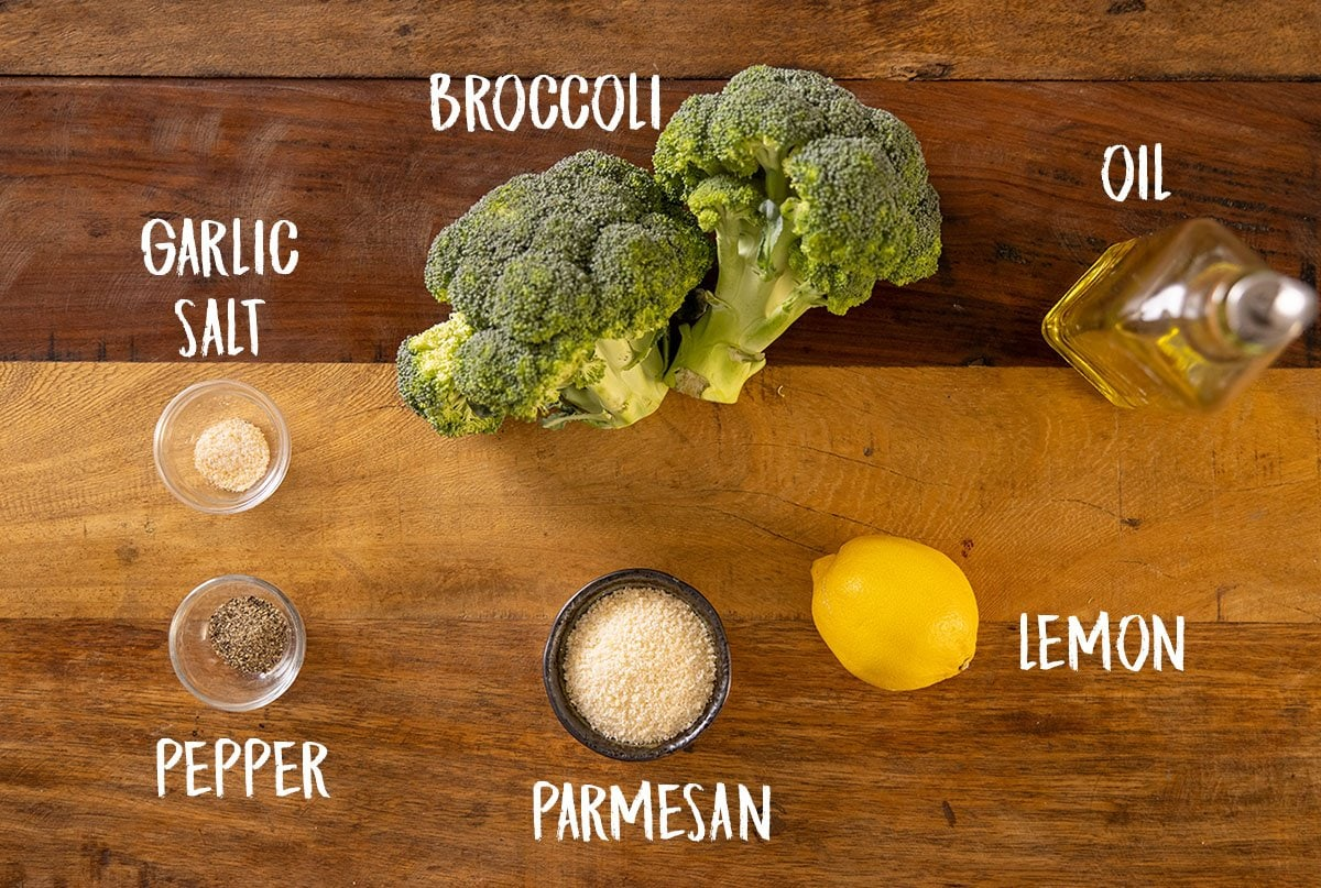 A wooden table with all of the ingredients laid out for roasted broccoli with garlic