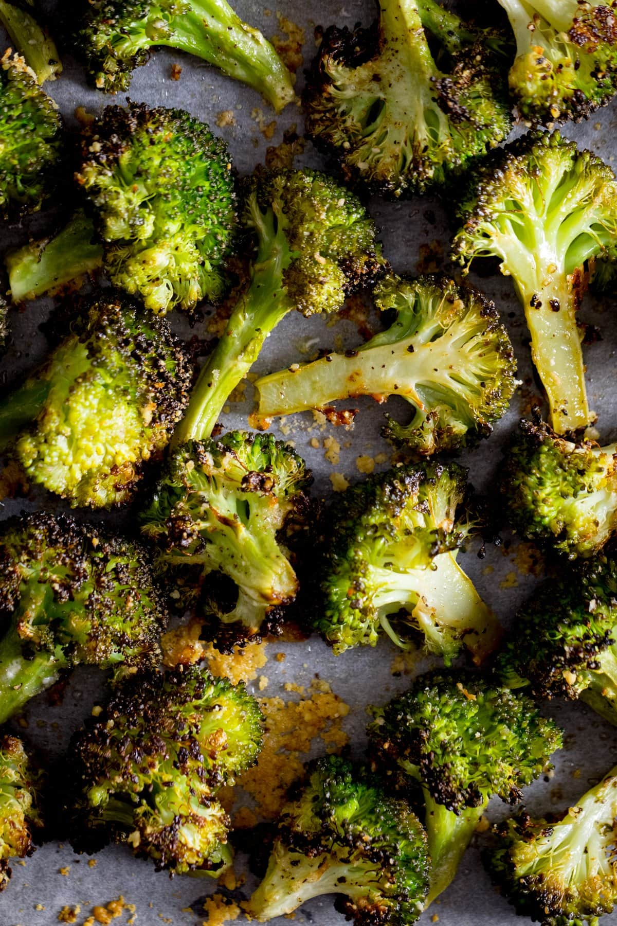 A close up of roasted broccoli with garlic on a white tray