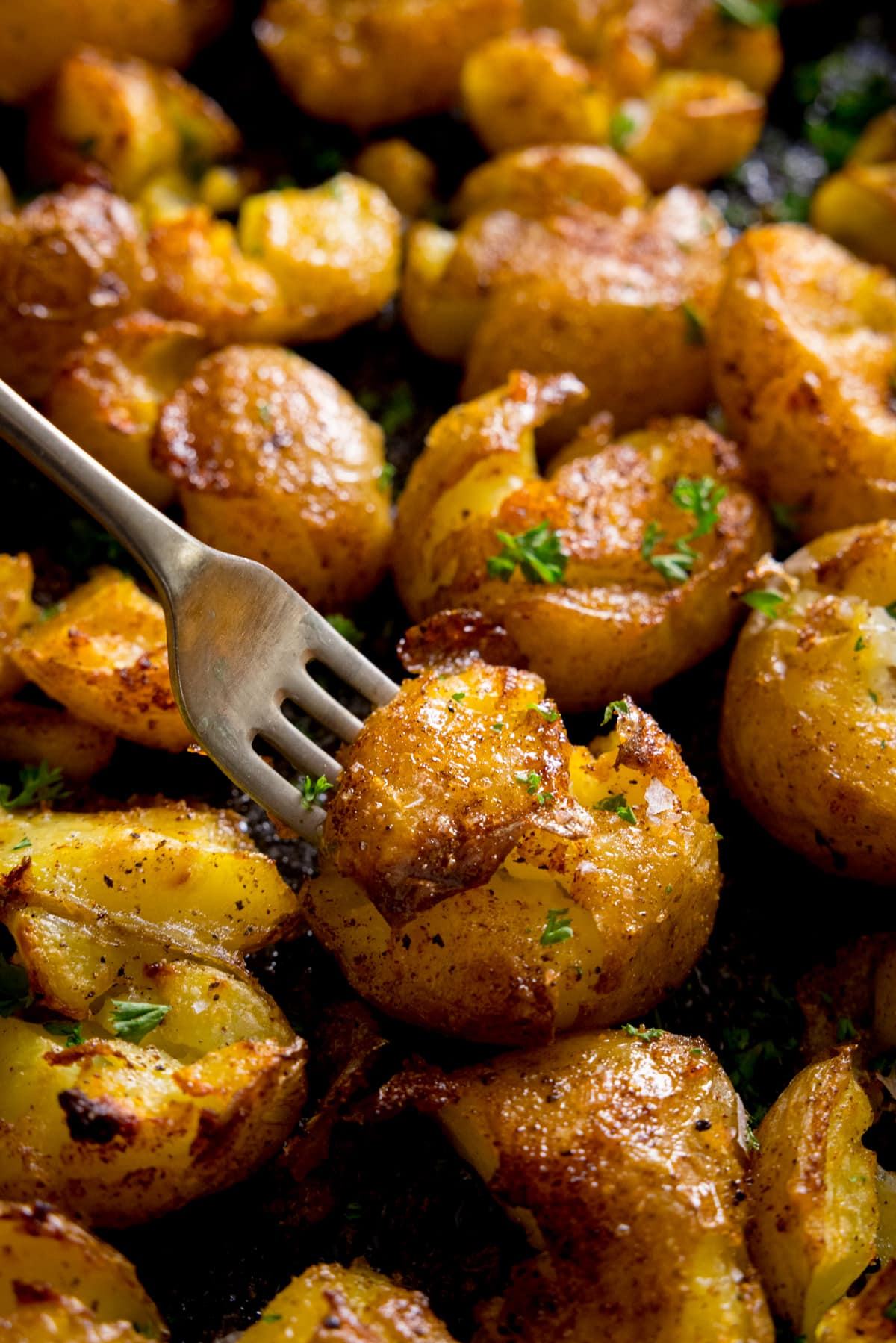A plate of crispy smashed potatoes with a fork digging into a potato
